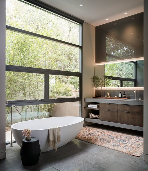 The master bath is complete with a deep soaking Agape Spoon XL bathtub. The outdoor area is enclosed for privacy, enabling the extensive glazing. J Geiger roller shades offer additional seclusion.