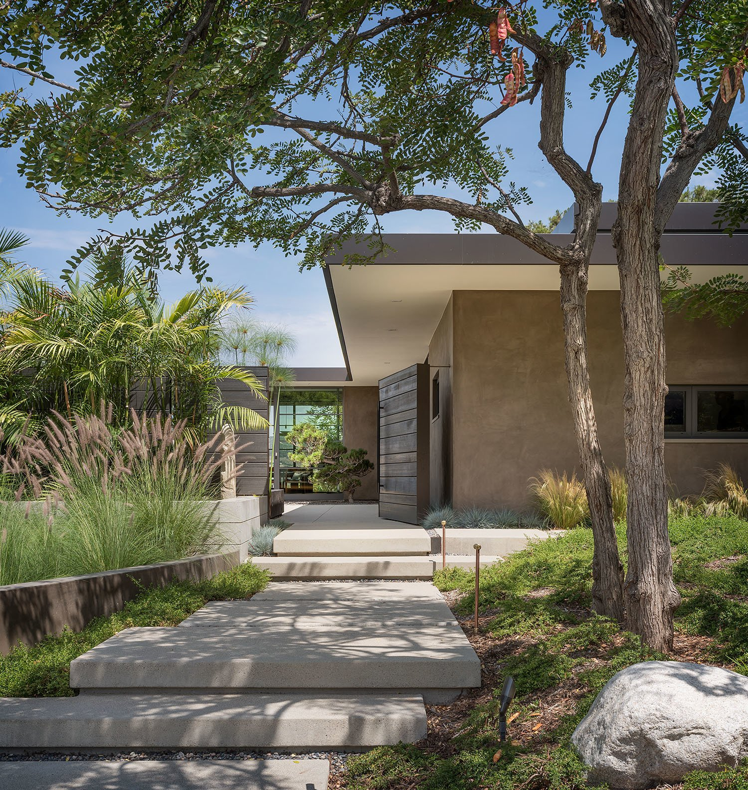 Exterior, Mid-Century Building Type, Flat RoofLine, Concrete Siding Material, and House Building Type The grand entrance to Woods Cove Retreat welcomes the homeowners and guests.  Photo 2 of 23 in A Southern California Midcentury Gets a Serene, Japanese-Inspired Treatment