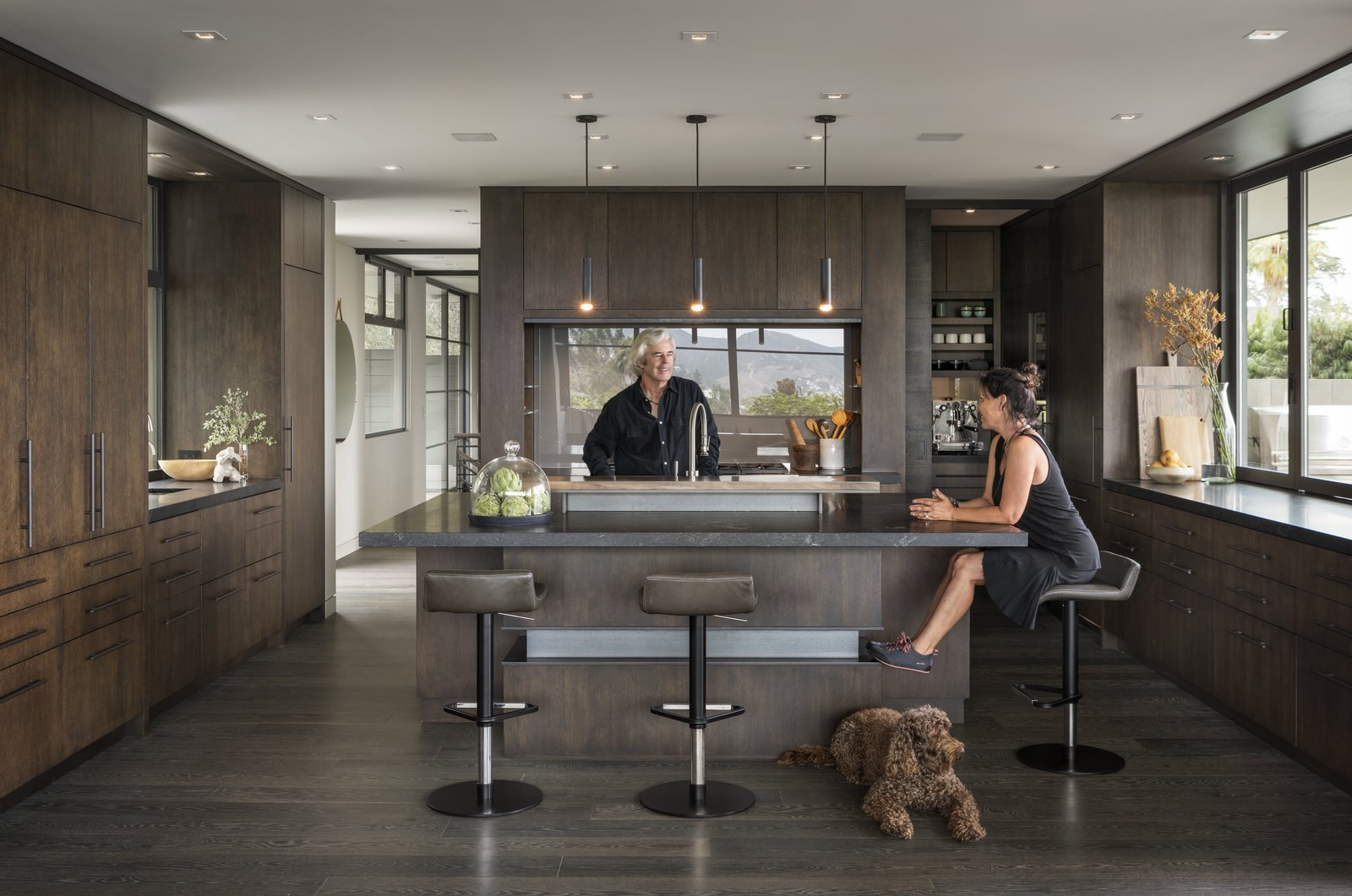 Kitchen, Ceiling Lighting, Dark Hardwood Floor, Pendant Lighting, Granite Counter, and Wood Cabinet The homeowners take a seat at the island of their kitchen.  Photo 11 of 23 in A Southern California Midcentury Gets a Serene, Japanese-Inspired Treatment