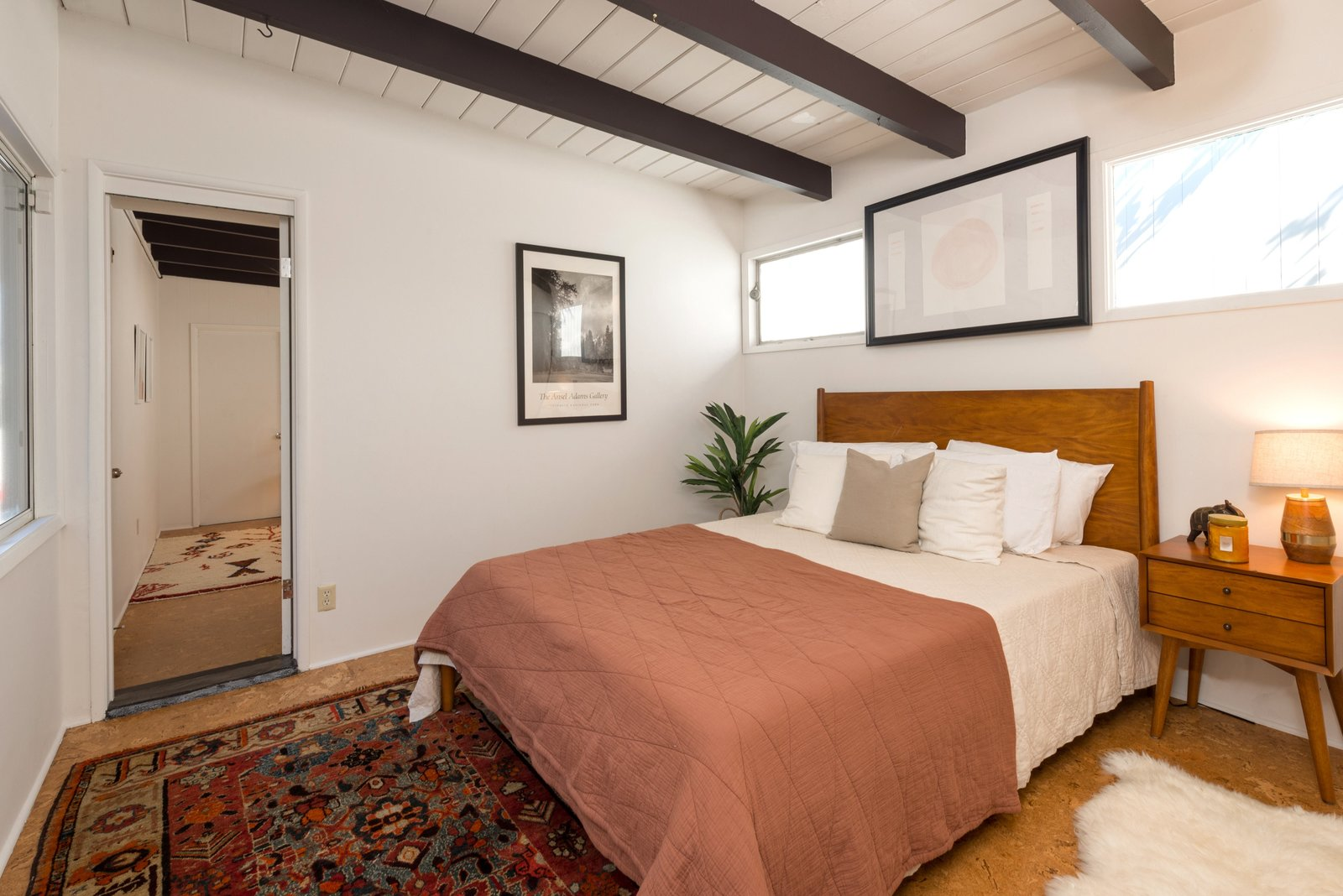 Bedroom, Bed, Table Lighting, Rug Floor, Cork Floor, and Night Stands The home features three bedrooms in a private wing and two full baths.  Photo 12 of 17 in Snag This Hollywood Hills Midcentury Home For $1M