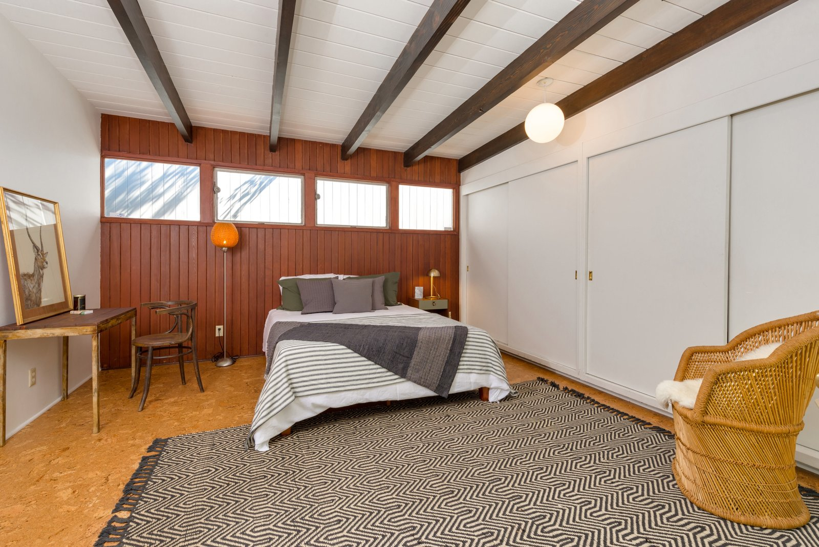 Bedroom, Chair, Pendant Lighting, Bed, Floor Lighting, Night Stands, Cork Floor, and Rug Floor The second bedroom has doors leading to the outdoor patio.  Photo 14 of 17 in Snag This Hollywood Hills Midcentury Home For $1M