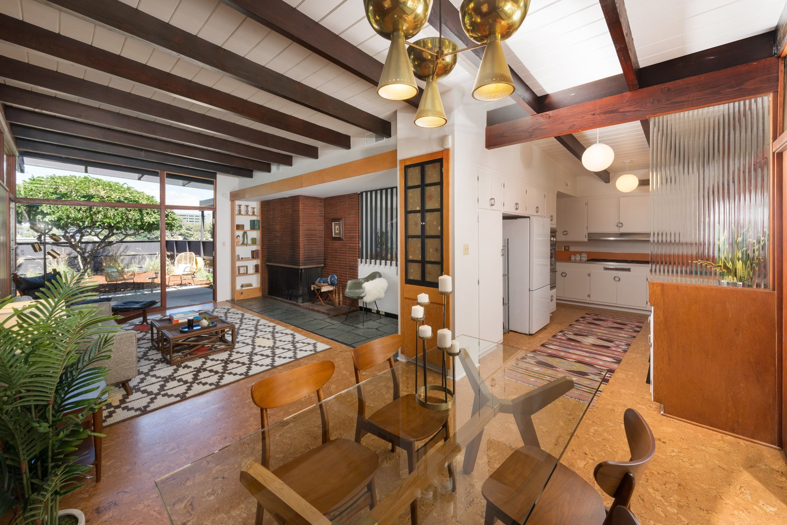 Dining Room, Table, Wood Burning Fireplace, Accent Lighting, Chair, Cork Floor, and Corner Fireplace The kitchen is just off the dining area.  Photo 9 of 17 in Snag This Hollywood Hills Midcentury Home For $1M