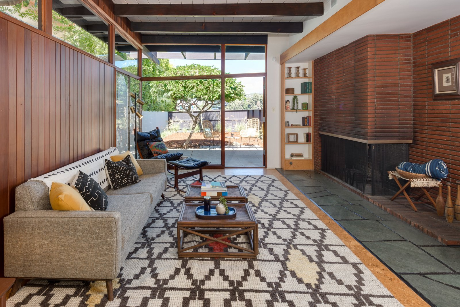 Living Room, Slate Floor, Sofa, Shelves, Coffee Tables, Rug Floor, Wood Burning Fireplace, Corner Fireplace, Cork Floor, and Chair The room extends straight out to the yard, with a wall of glass creating a seamless connection.  Photo 5 of 17 in Snag This Hollywood Hills Midcentury Home For $1M