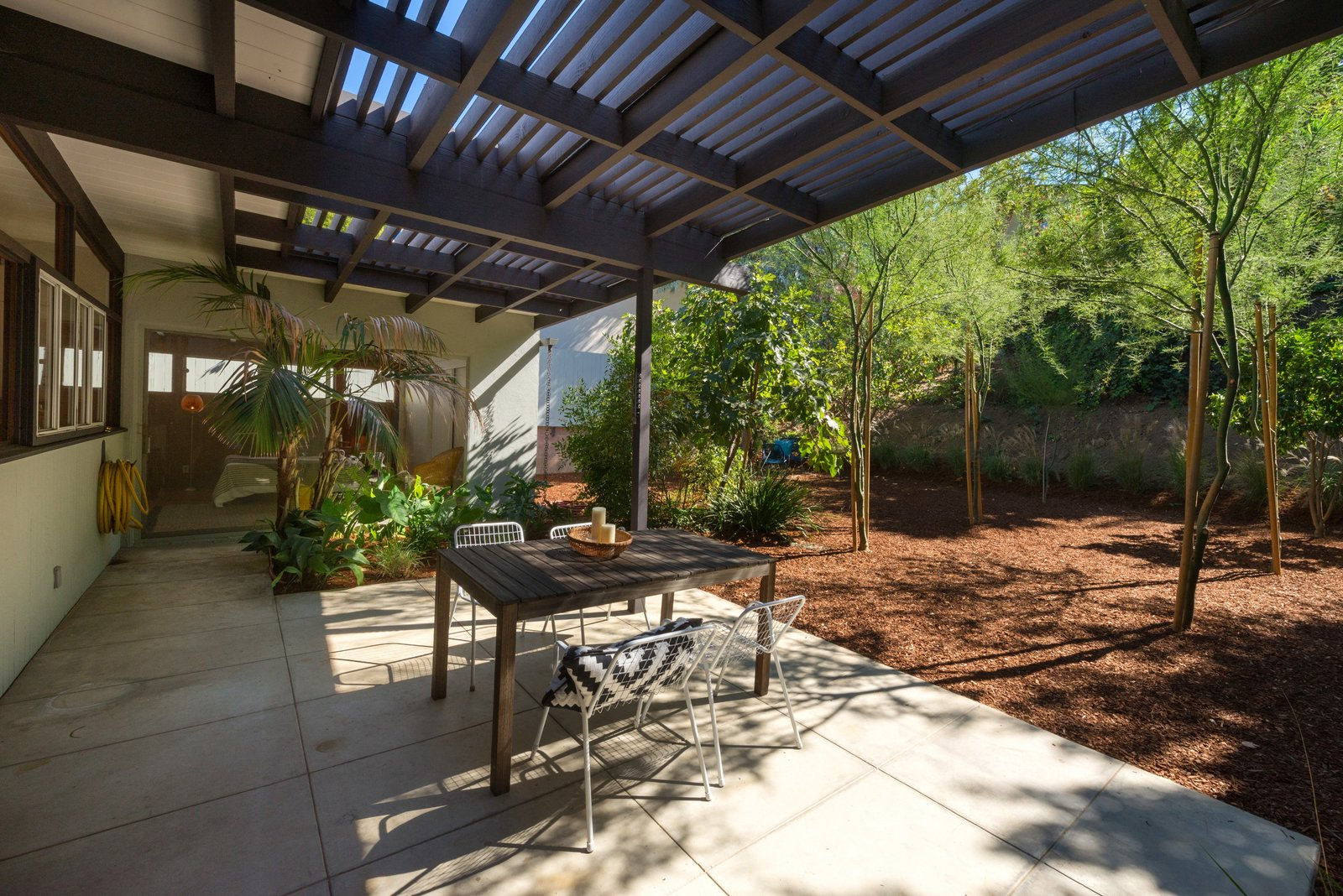 Outdoor, Side Yard, Large Patio, Porch, Deck, and Trees The patio features space for al fresco dining.  Photo 15 of 17 in Snag This Hollywood Hills Midcentury Home For $1M