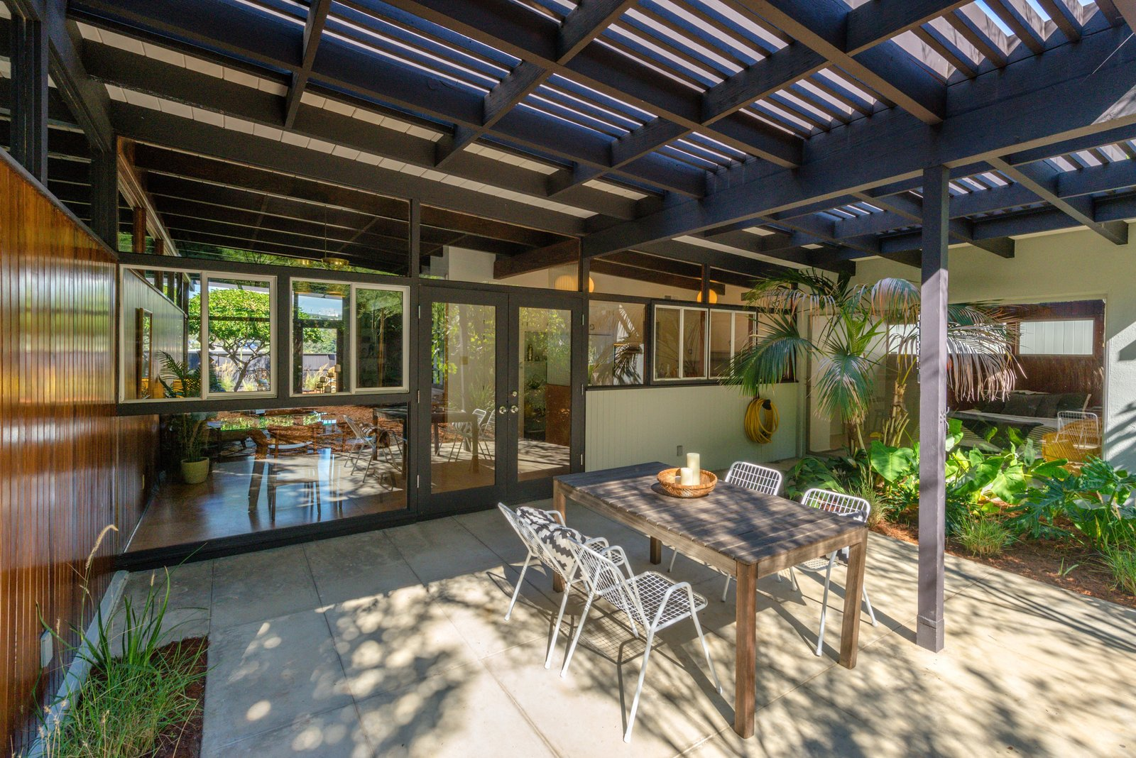 Outdoor, Large Patio, Porch, Deck, Side Yard, Shrubs, Hardscapes, Gardens, and Trees The outdoor space.  Best Photos from Snag This Hollywood Hills Midcentury Home For $1M