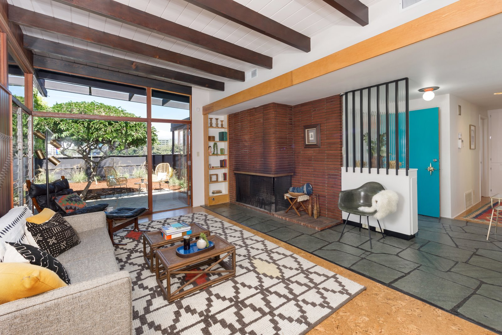 Living Room, Corner Fireplace, Chair, Ceiling Lighting, Coffee Tables, Sofa, Slate Floor, Wood Burning Fireplace, Rug Floor, Shelves, and Cork Floor The open-plan living space is anchored by a horizontal brick-inlay fireplace.     Photo 3 of 17 in Snag This Hollywood Hills Midcentury Home For $1M