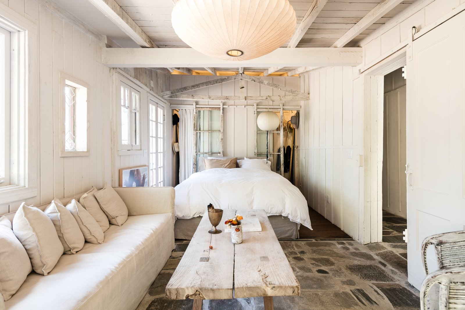 Bedroom, Medium Hardwood, Bed, Slate, and Pendant The bedroom has a comfortable, cozy feel—a Nelson bubble lamp gives the space a warm glow.     Best Bedroom Slate Bed Medium Hardwood Pendant Photos from Leanne Ford's Vintage Echo Park Cabin Hits the Market at $995K