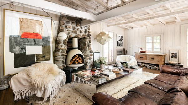 The cozy living room has a modern bohemian sense of style but is still firmly anchored to the  home's past through the stone inlay hearth.