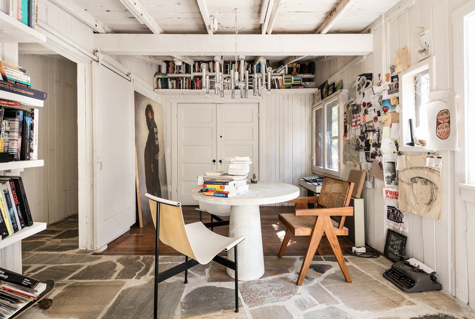 Office, Study, Medium Hardwood, Chair, Bookcase, and Slate The mixed material palette of stone and wood is present throughout the home.  Best Office Study Bookcase Photos from Leanne Ford's Vintage Echo Park Cabin Hits the Market at $995K