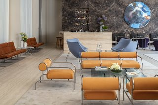 The lobby's historic elements are juxtaposed with classic midcentury designs from Shiro Kuramata and Pierre Paulin together with artwork by Damien Hirst.