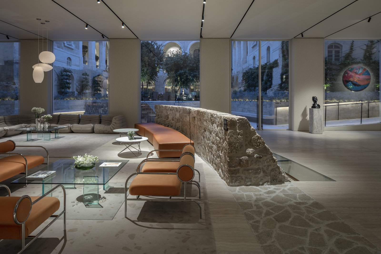 Living Room, Bench, Chair, Coffee Tables, Sofa, Pendant Lighting, and Track Lighting The bastion wall has been incorporated into the lobby's design.   Jaffa Hotel from John Pawson Turns an Old Hospital and Convent Into a Luxe Hotel in Israel