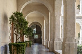 A series of arches and colonnades lead to a secluded central courtyard situated between the old structures and Pawson's new addition.