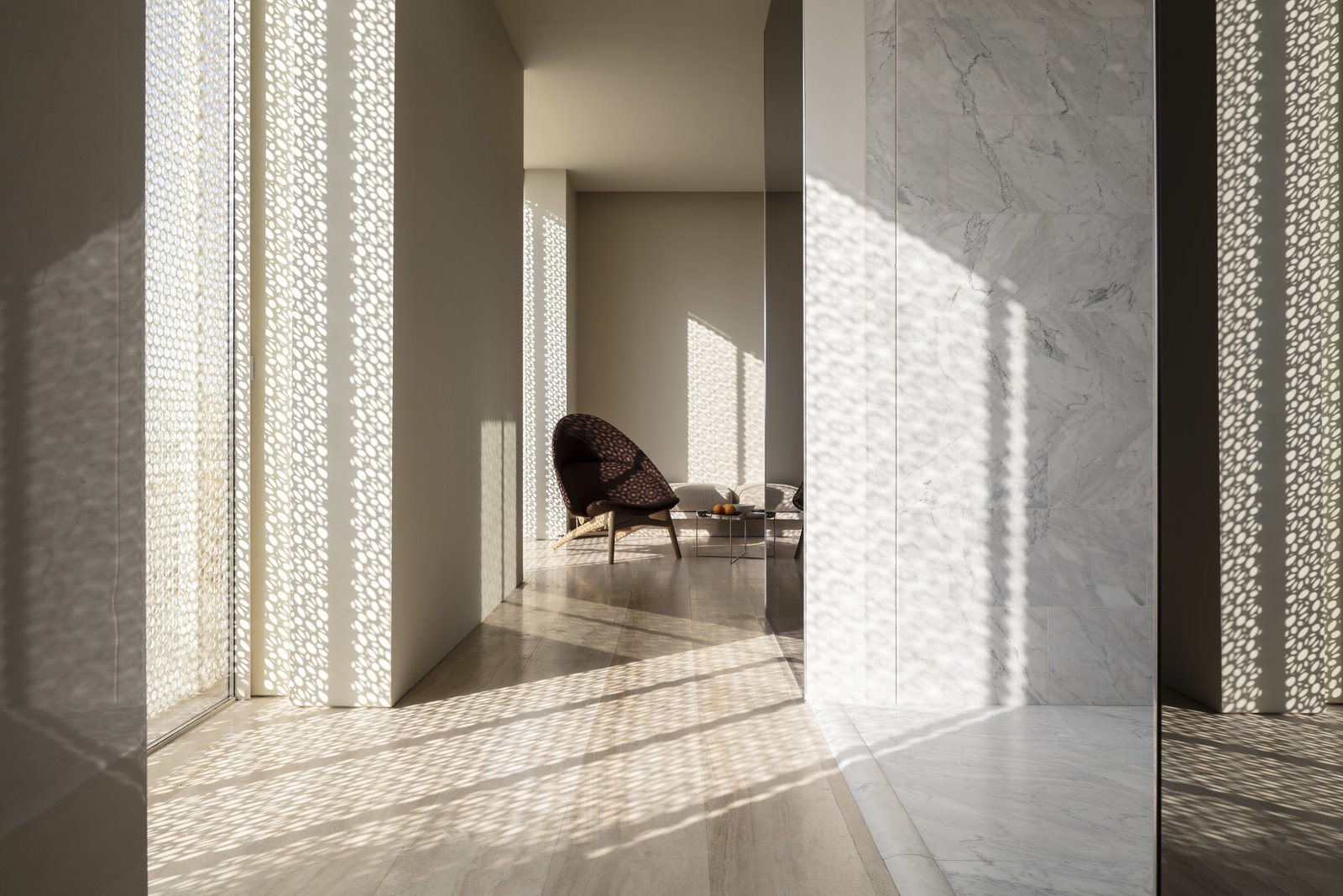 Bedroom, Chair, and Light Hardwood Floor Throughout the hotel, patterned screens known as Masharabiya complement contemporary motifs and patterns—Pawson's homage to traditional Middle Eastern architecture.   Jaffa Hotel from John Pawson Turns an Old Hospital and Convent Into a Luxe Hotel in Israel