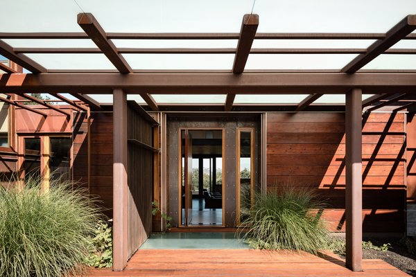 The façade juxtaposes the rich oxidized patina of Cor-ten steel with the deep, earthy tones of reclaimed redwood beams.