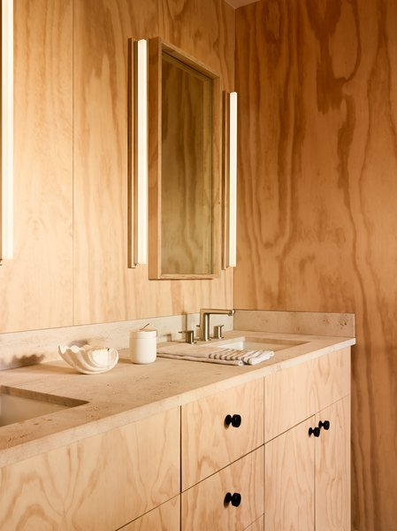 The master bath is clad in plywood and features a custom vanity by Woodline Design paired with a Bourgogne limestone countertop with a honed finish by Fox Marble. The vanity mirror is a custom piece by Greg Nelson at GGD.