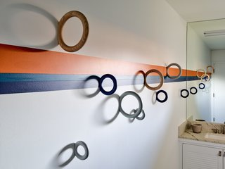 The kids' bathroom features bold, colorful stripes and Gym Hooks from the Danish Design Store.