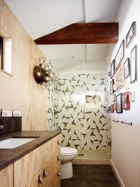 An exposed beam adds depth and character to one of the guest bathrooms while graphic tiles echo the complex geometries of an extensive collection of butterflies that is on display.