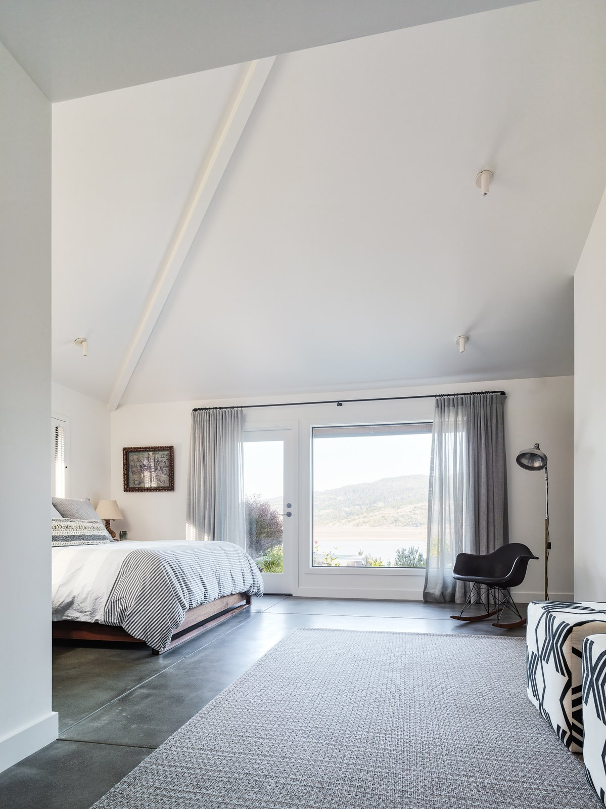 Bedroom, Bed, Floor, Chair, Rug, Table, Ceiling, Concrete, Lamps, and Rockers The bright and airy master bedroom features high ceilings and a spectacular view.  Best Bedroom Ceiling Chair Rockers Photos from A Delicate Renovation Revives a '70s Beach House in Northern California