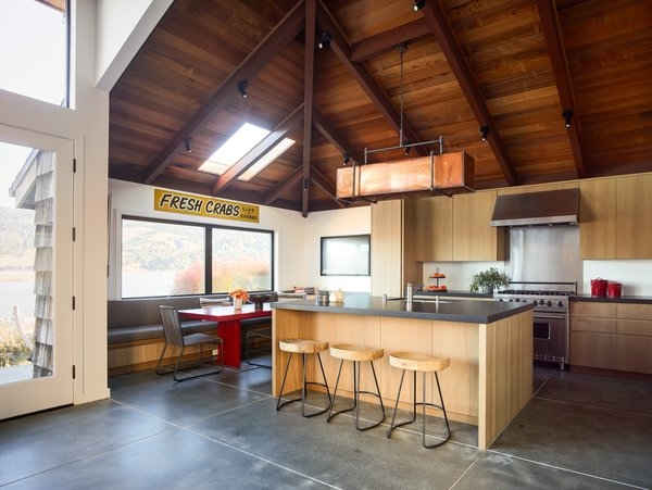 The kitchen features the original wood-paneled ceiling, polished concrete floors, custom cabinetry from Woodline Design, a black granite countertop, and stools from Restoration Hardware.