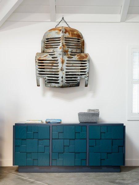 A vintage car grill serves as a found art installation.