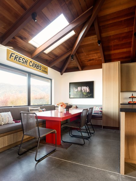 "For the dining nook, Woodline Design created a custom table and banquette featuring cushions wrapped in Great Outdoors Shale fabric. The chairs are the Harp 349 by Roda. The ""Fresh Crabs"" sign adds a beachy, folk art feel."