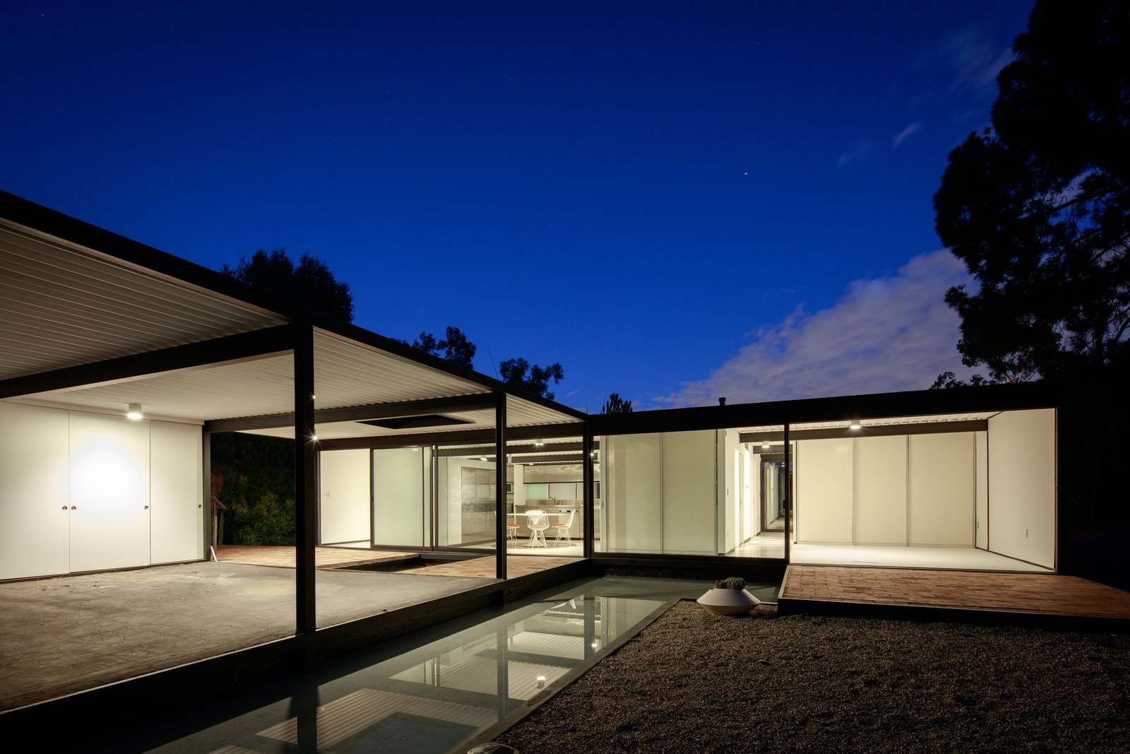 Exterior, Mid-Century Building Type, Metal Siding Material, House Building Type, Flat RoofLine, and Glass Siding Material The home at dusk.  Photos from This Pierre Koenig-Designed Case Study House Lists For $3.6M