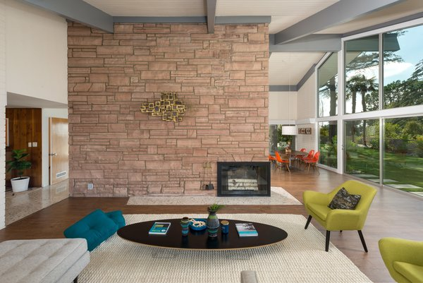 The open-plan living space is anchored by a grand dual-sided fireplace. Extensive glazing brings a strong sense of the outdoors in and keeps the interiors bright and airy.