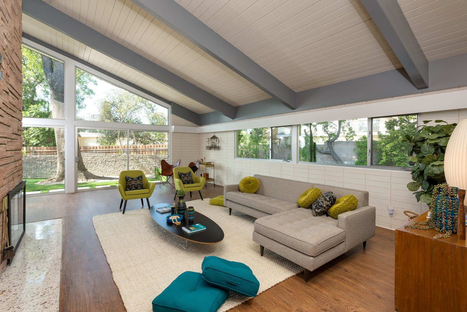 Living, Coffee Tables, Sofa, Medium Hardwood, Two-Sided, Terrazzo, Chair, and Wood Burning The tongue-and-groove ceiling is another classic midcentury feature.  Living Two-Sided Sofa Coffee Tables Terrazzo Photos from Step Back in Time in This Midcentury Now Asking $1.4M