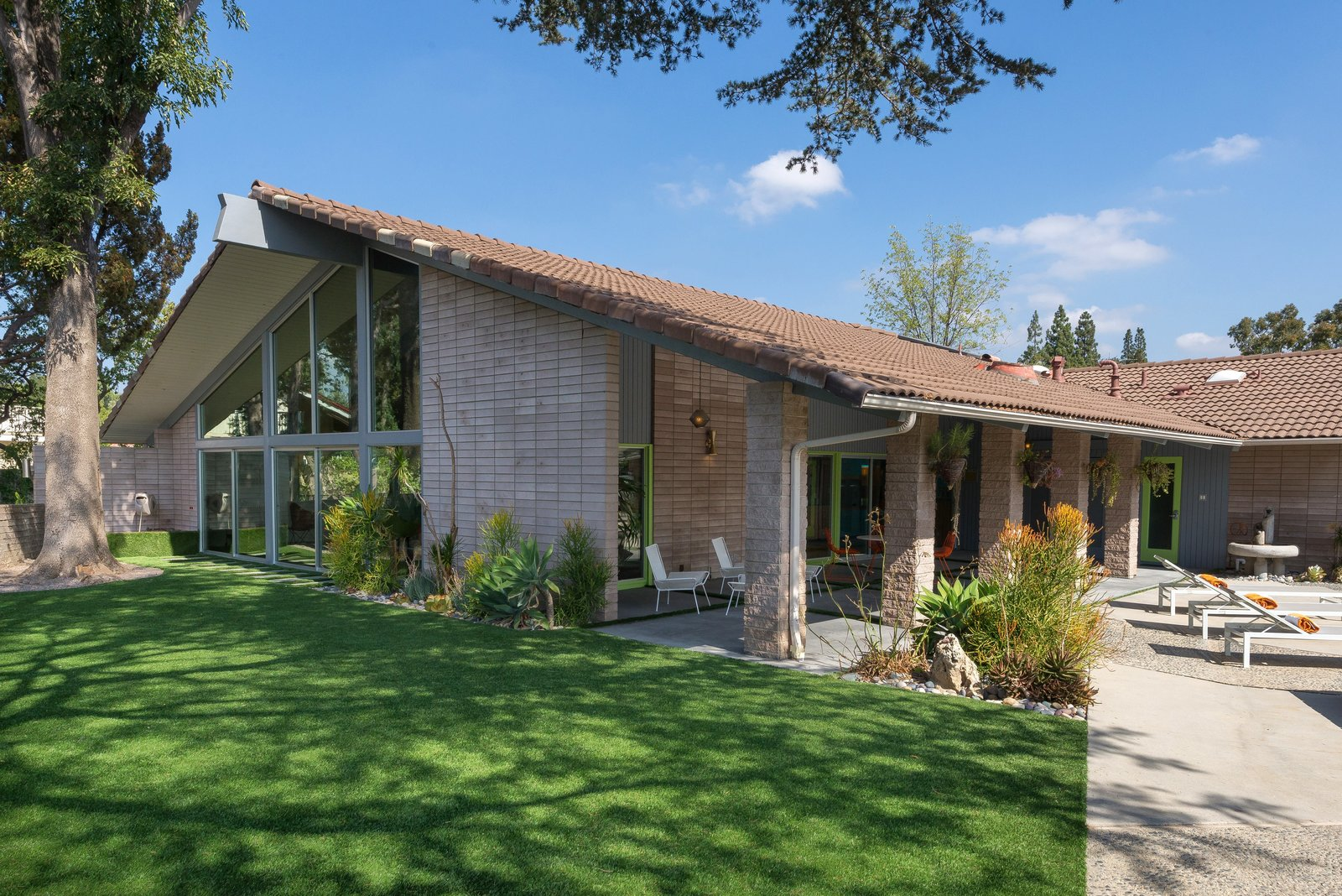 Exterior, House, Mid-Century, Brick, Gable, Glass, and Shingles The outdoor space has been landscaped with synthetic turf, as well as drought-tolerant plants.    Best Exterior Shingles Glass Brick Photos from Step Back in Time in This Midcentury Now Asking $1.4M