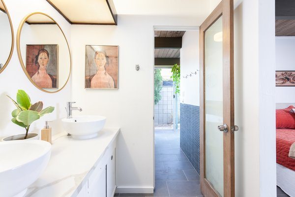 The master bathroom has been expanded and features an indoor-outdoor shower space.