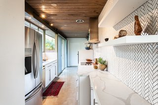 The updated kitchen features a lovely tile backsplash and polished concrete floors.