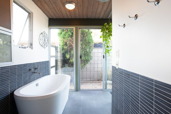Beautifully tiled, the freestanding soaking tub is an excellent addition to the space.