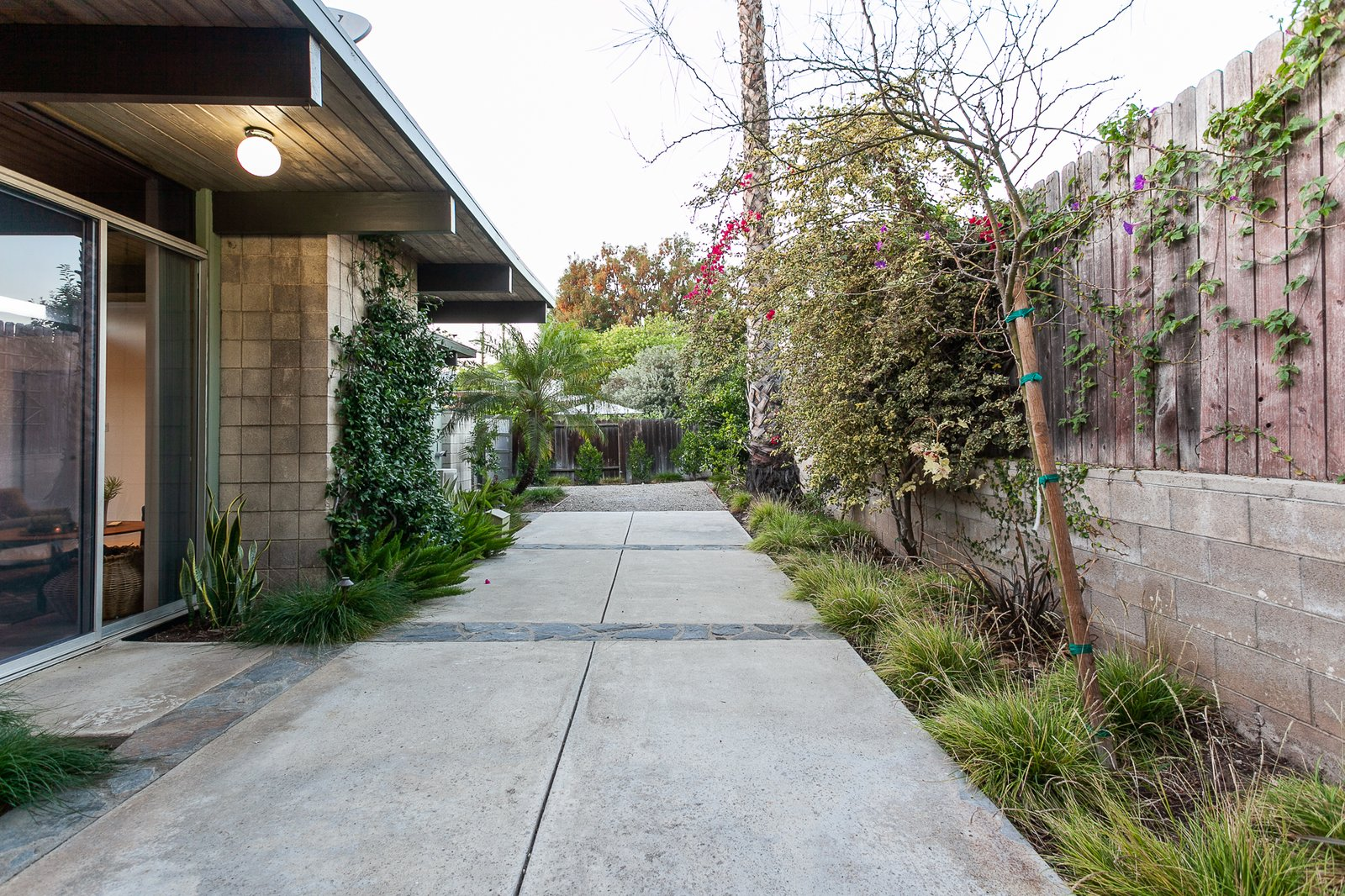 Outdoor, Large, Vertical, Pavers, Concrete, Side Yard, Stone, Concrete, Wood, Horizontal, Hanging, Trees, and Shrubs The home's elegant post-and-beam construction as seen from the exterior.    Outdoor Side Yard Concrete Large Hanging Photos from An Updated Eichler With an Indoor-Outdoor Master Bath Seeks $1.15M
