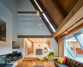 The soaring vaulted ceiling and the spirit of the living room were preserved, and the entire lower level was enhanced by opening up the space, creating a smooth flow from the living room into the kitchen and dining areas.