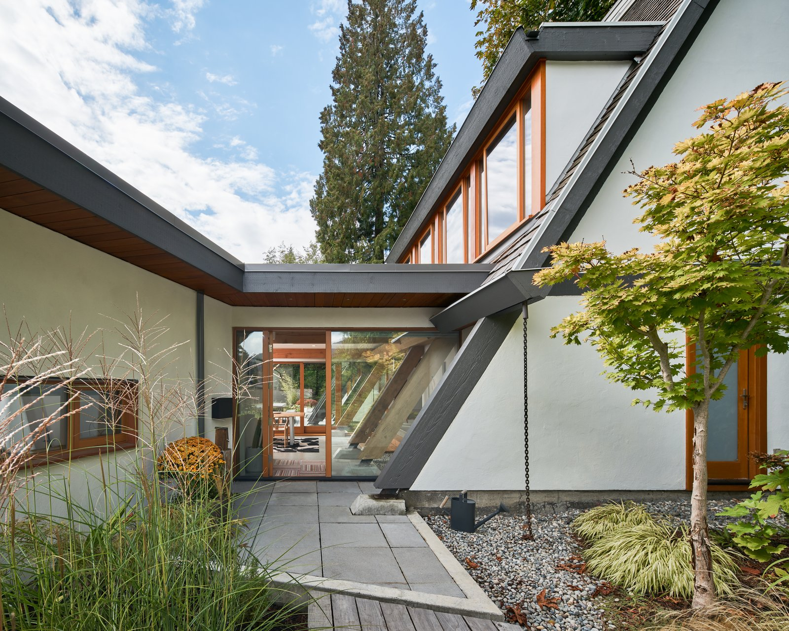 "The addition is connected to the existing home by a glass ""bridge"" that serves as the entry and maintains visual continuity through to the backyard."
