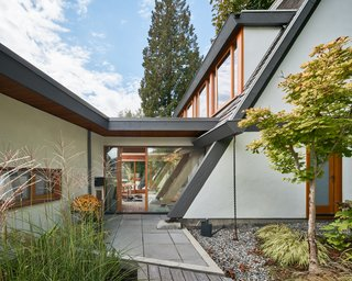 """The addition is connected to the existing home by a glass """"bridge"""" that serves as the entry and maintains visual continuity through to the backyard."""