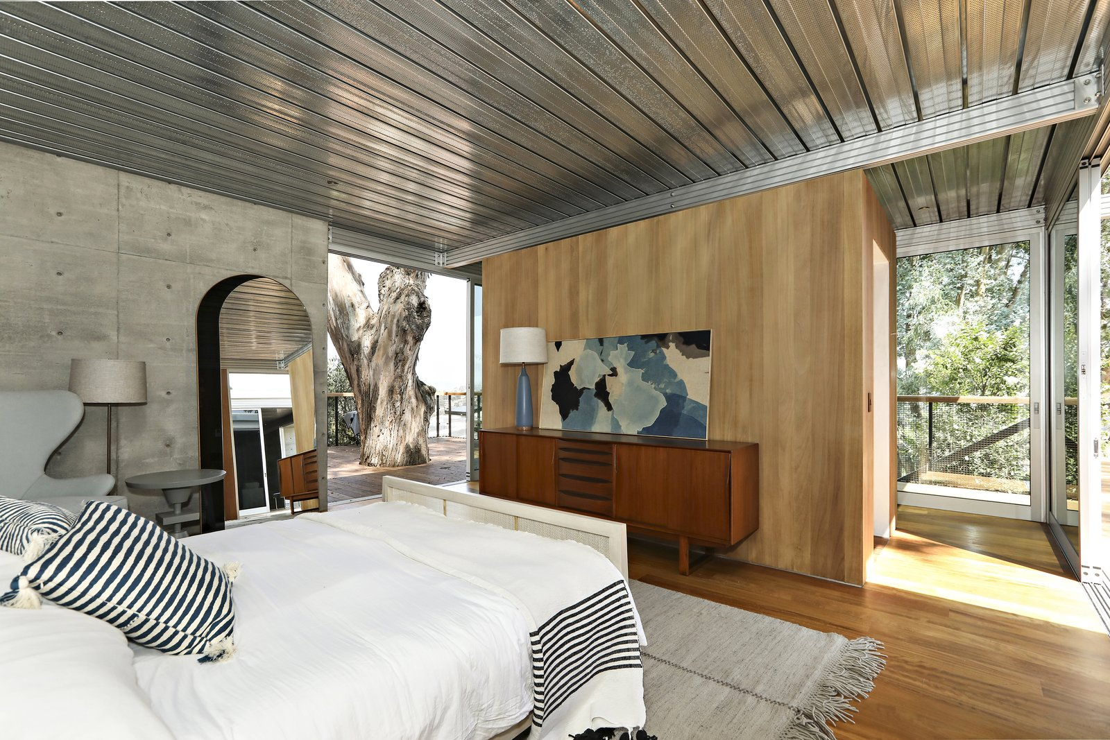 Bedroom, Dresser, Bed, Table Lighting, Chair, Medium Hardwood Floor, Night Stands, Rug Floor, Floor Lighting, and Lamps A look at one of the three bedrooms, which is bright, airy, and has a tasteful mix of luxe materials.     Photos from A Thoughtfully Updated Hillside Home in L.A. Lists For $5.12M