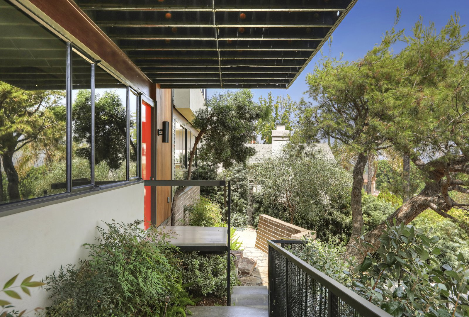Outdoor, Pavers, Shrubs, Trees, Small, Walkways, Stone, Metal, Horizontal, Hanging, Boulders, Retaining, and Front Yard The entrance showcases the home's clean midcentury lines.     Outdoor Boulders Trees Metal Hanging Front Yard Small Photos from A Thoughtfully Updated Hillside Home in L.A. Lists For $5.12M