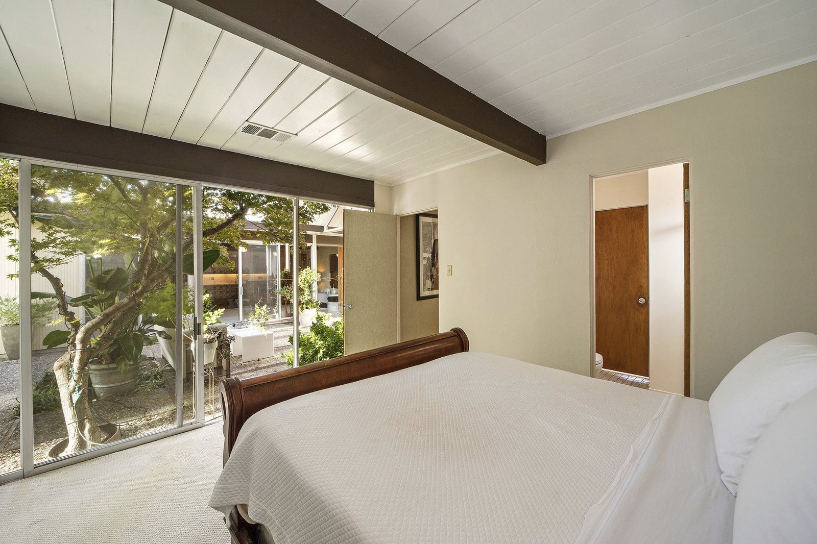 Bedroom, Carpet Floor, and Bed The master bedroom features an ensuite bathroom and opens via sliding doors to the atrium.  Photo 12 of 13 in A Double A-Frame Eichler in the Bay Area Asks $925K