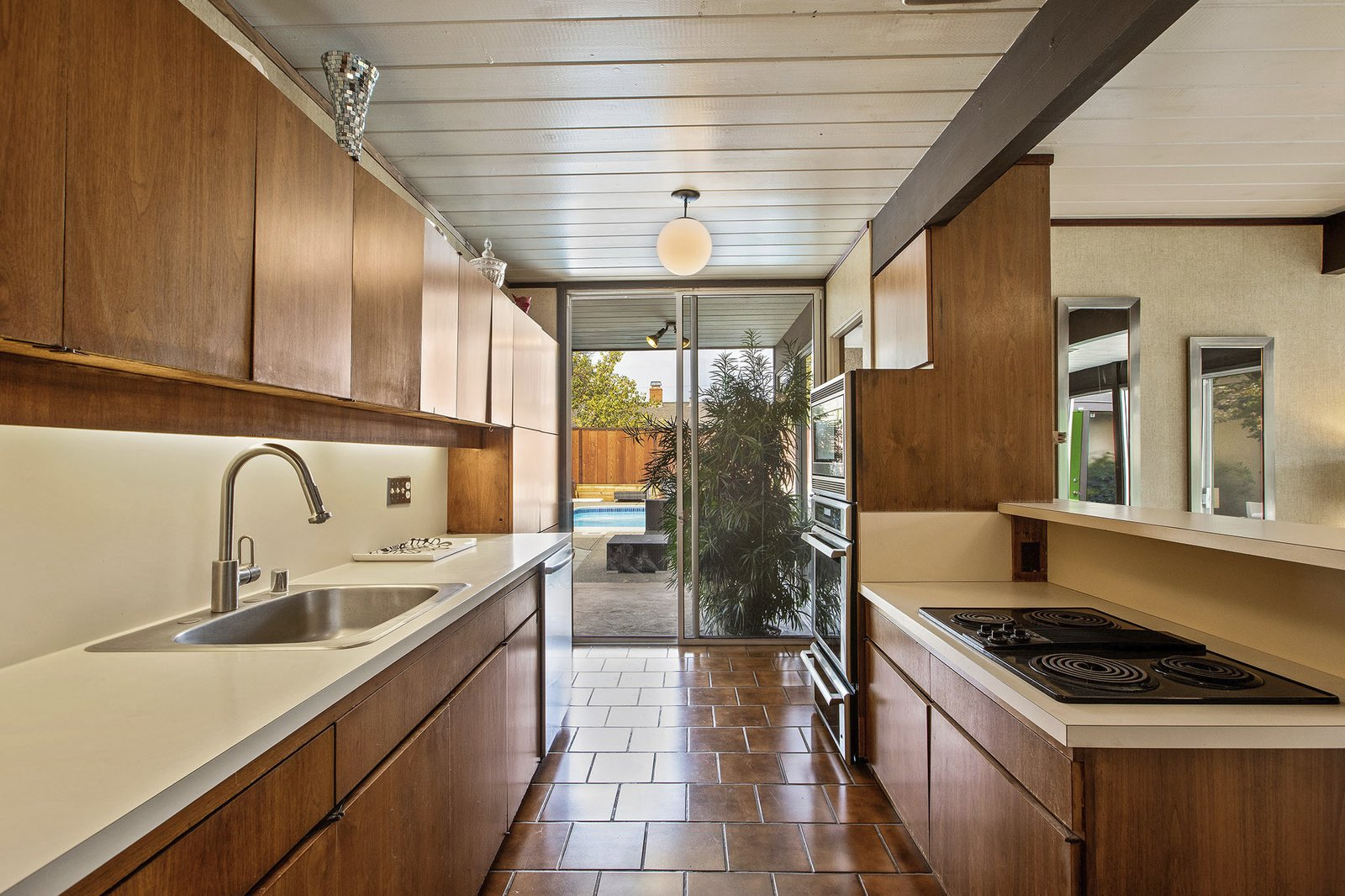 Kitchen, Drop In Sink, Pendant Lighting, Cooktops, Wood Cabinet, Laminate Counter, Wall Oven, Microwave, and Ceramic Tile Floor Sliding glass doors in the kitchen open to the outdoors.  Photo 11 of 13 in A Double A-Frame Eichler in the Bay Area Asks $925K