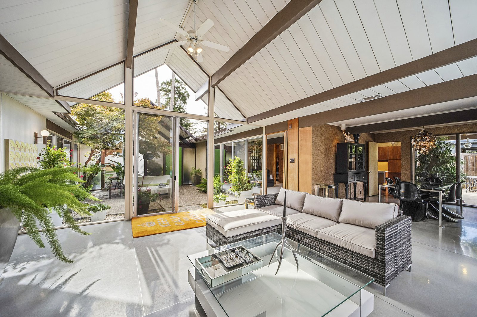Living Room, Concrete Floor, Ceiling Lighting, Sectional, Coffee Tables, and End Tables A look at the light-filled living space.   Photo 6 of 13 in A Double A-Frame Eichler in the Bay Area Asks $925K
