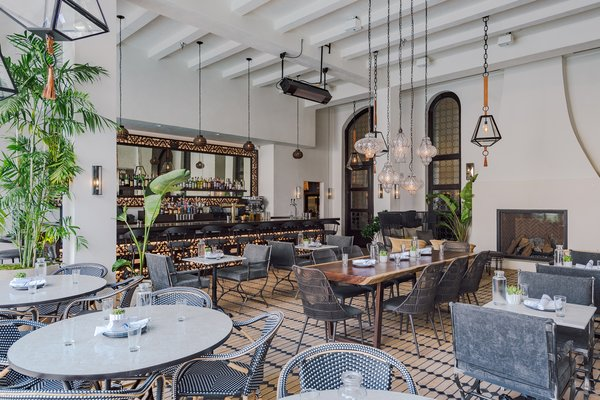 Overlooking the pool is Veranda, an al fresco dining venue. The design team restored and expanded the hotel's original 1920s fireplace with a double-sided feature, adding a historic touchpoint to the new dining space.