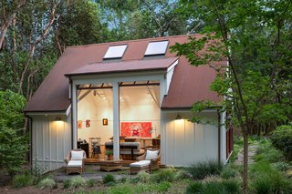 The light-filled indoor/outdoor art studio features large window-paned garage-doors, which open the space to its verdant surroundings.