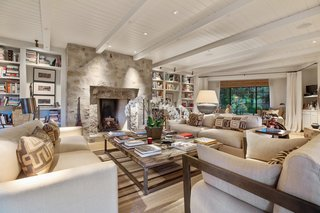 The living room features a wood-burning fireplace, as well as a tongue-and-groove ceiling that has been painted white.