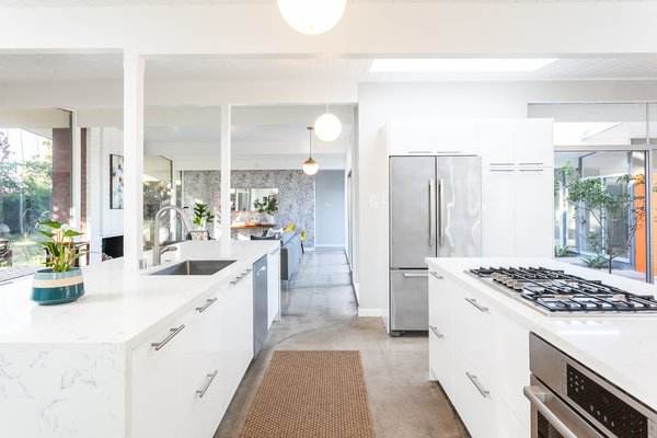 The renovated kitchen features a sleek island-peninsula, allowing seamless indoor/outdoor flow from the glass-walled exterior to the inner atrium.