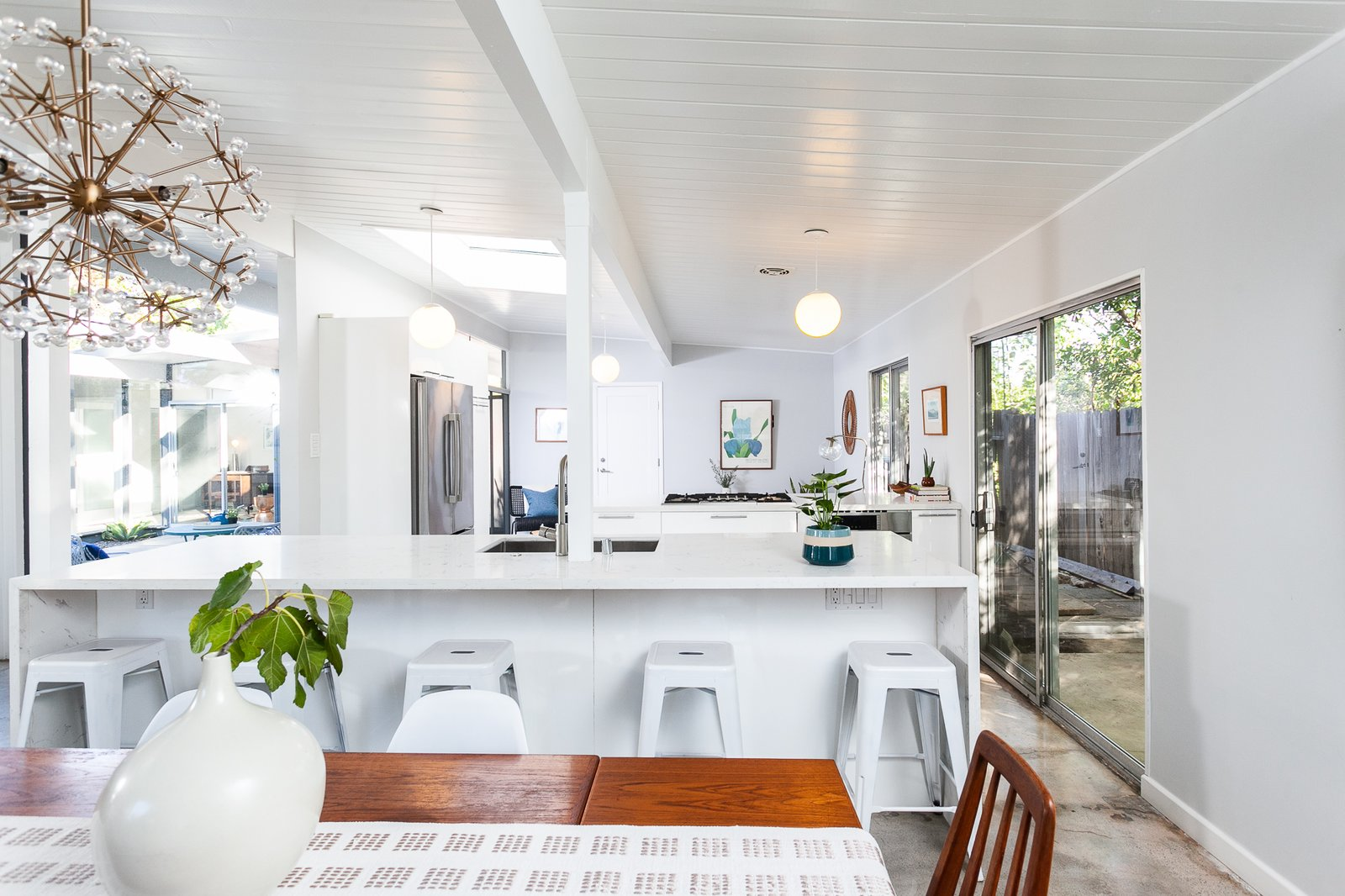 Dining, Chair, Table, Stools, Concrete, Pendant, and Bar The kitchen features period-appropriate globe pendant lighting.  Best Kitchen Concrete Undermount Refrigerator White Photos from This Light-Filled Orange County Eichler Home Just Listed For $1.1M