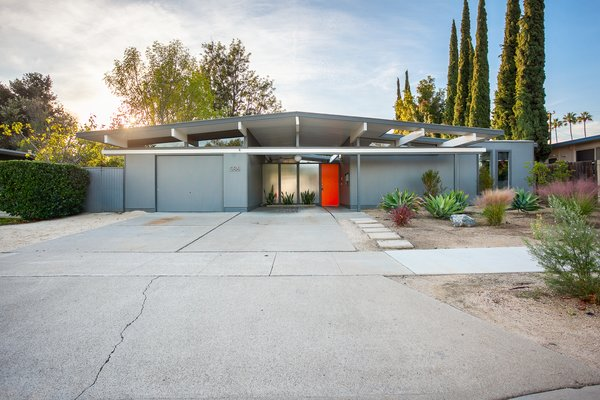 Classic post-and-beam construction and a bright orange door create a sunny facade for this updated Orange County Eichler.