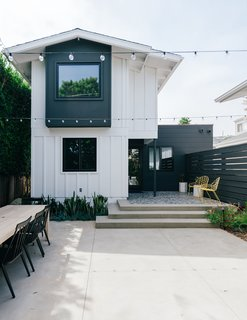 """MYD Studio updated the exterior with a mix of black and white siding. They expanded the master bedroom on the second level and remodeled the den on the first floor into an additional bedroom. A new """"black box"""" addition houses a third bedroom."""
