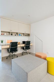 The new study lounge features ceramic tile flooring from Ann Sacks along with a custom plywood desk with a Formica top, Eames desk chairs, and an ottoman from Blue Dot.