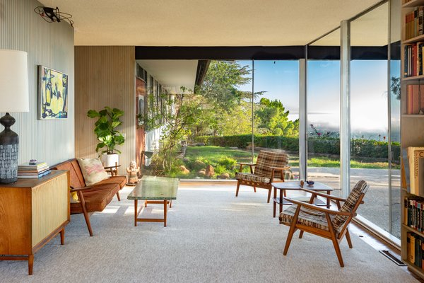 The midcentury modern home features wraparound glass walls.